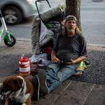 Homeless man sitting down