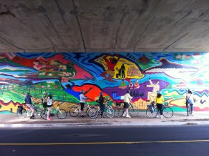 Bikers (potential customers), looking at a mural on the BeltLine path (click for source)