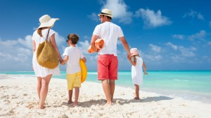 Back view of a happy family on tropical beach; Shutterstock ID 152536469; PO: today-daivd