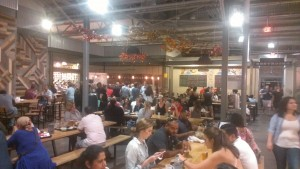 People eat at family-style tables in Krog Street Market