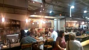 Patrons socialize at a crowded bar inside Krog Street Market