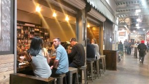 People drink, talk, and eat at a bar connected to a restaurant inside Krog Street Market