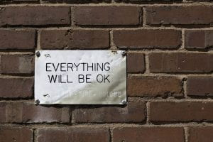 Metal sign on brick with Everything Will Be Okay written on it
