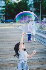 Girl joyfully pops giant soap bubble
