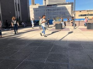 a wide shot of people walking through or sitting down in the courtyard