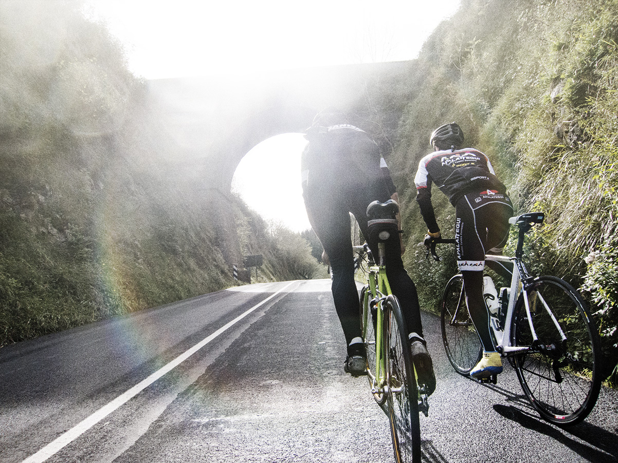 Two people on bicycles riding on a road approaching a tunnel. Sun is causing glare and reflection off the camera.