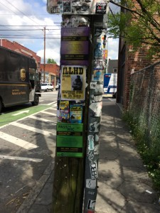 Pole on Edgewood Ave covered in flyers for open mic nights and performances in Department Store and around the city