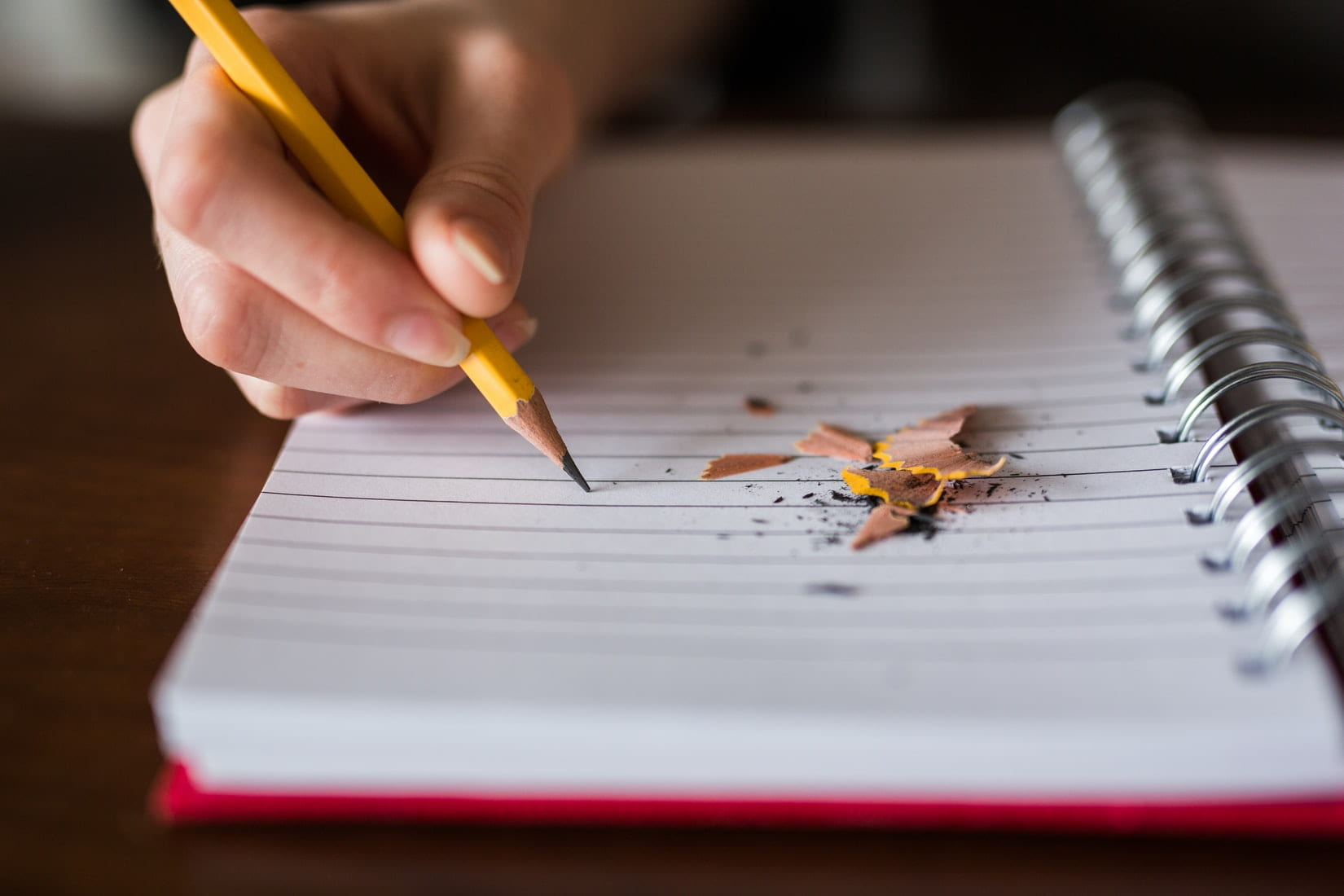 A person is holding a pencil tighly and the led is breaking and there are shavings all over an empty page.