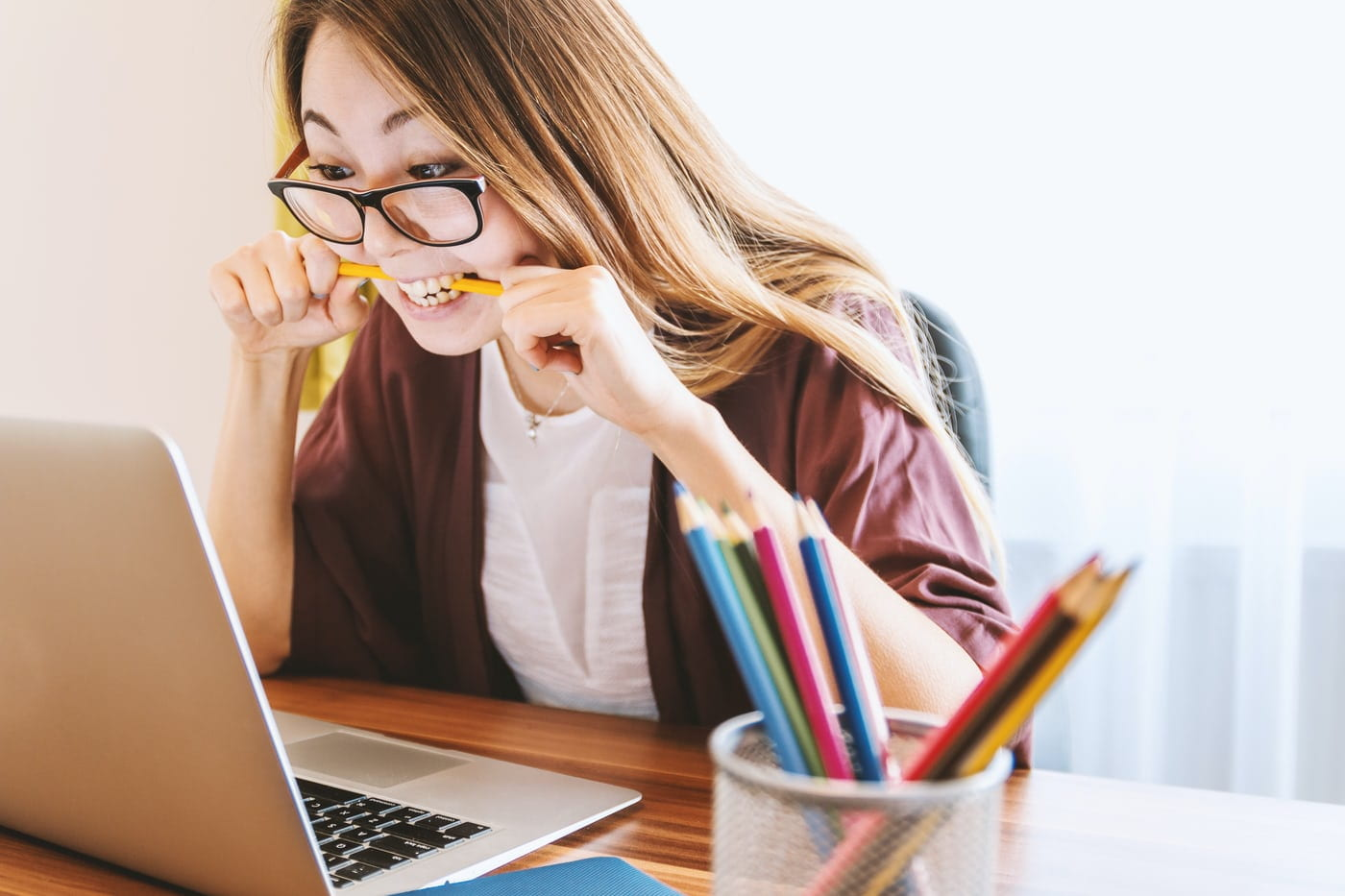 Picture of student at computer with her pen between her teeth and a nervous look on her face.