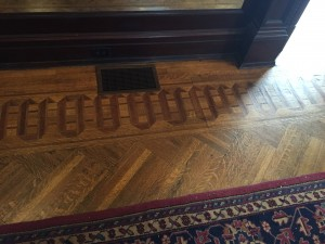 The perimeter of the living room floor is lined with intricate patterns using woods of different shades