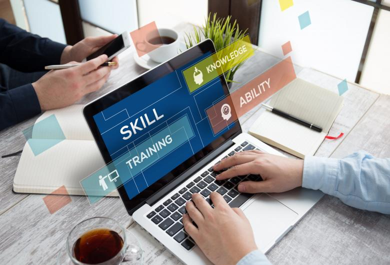 open laptop with the words skill, knowledge, training & ability on the screen, hands on the keyboard