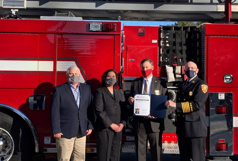Standing before Apex fire truck, North Carolina Insurance Commissioner and State Fire Marshal Mike Causey presents the new ratings to Wake County and Apex officials.