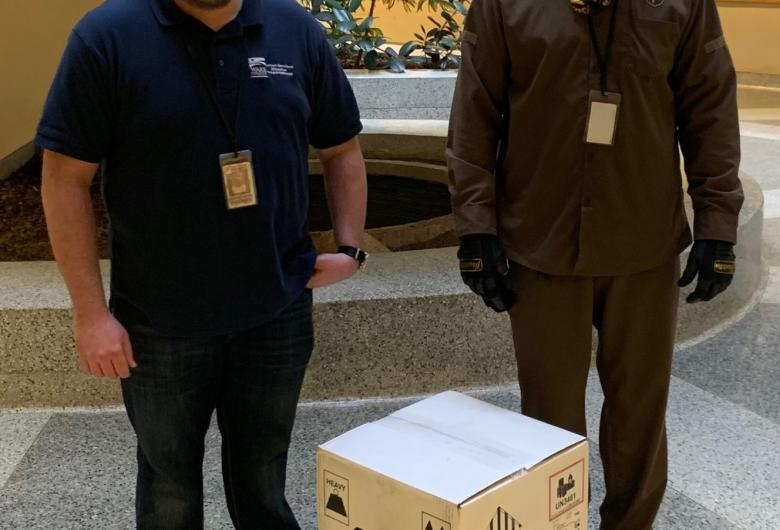 Wake County Public Health employee and a UPS driver stand with a box of COVID-19 vaccine.