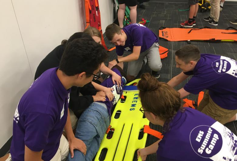 Camp participants putting patient on a long spine board.