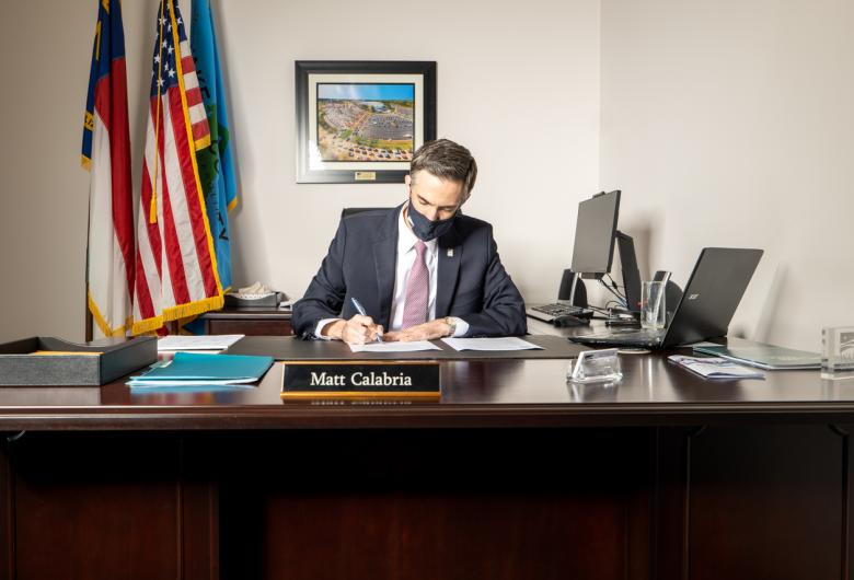 Commissioners Chair Matt Calabria signs mask mandate at his desk