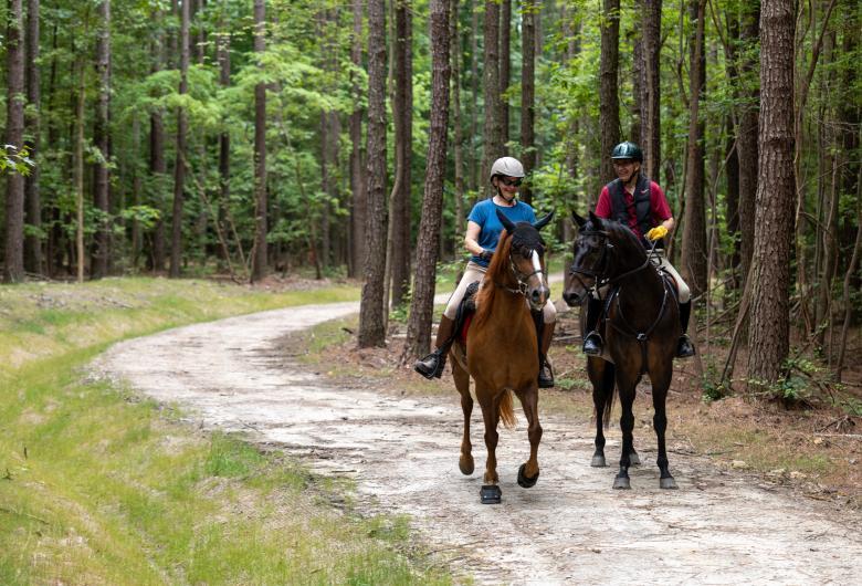 Two horseback riders smiling