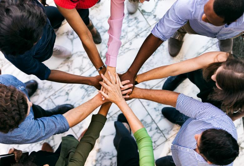 Team of diverse workers puts hands in together
