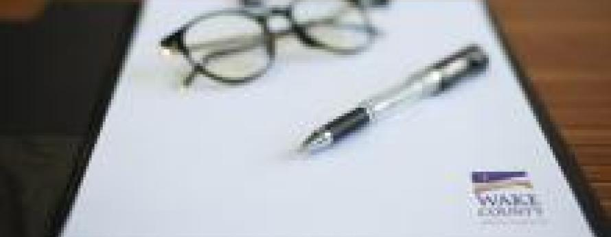 Glasses, a pen and Wake County letterhead rest on a table
