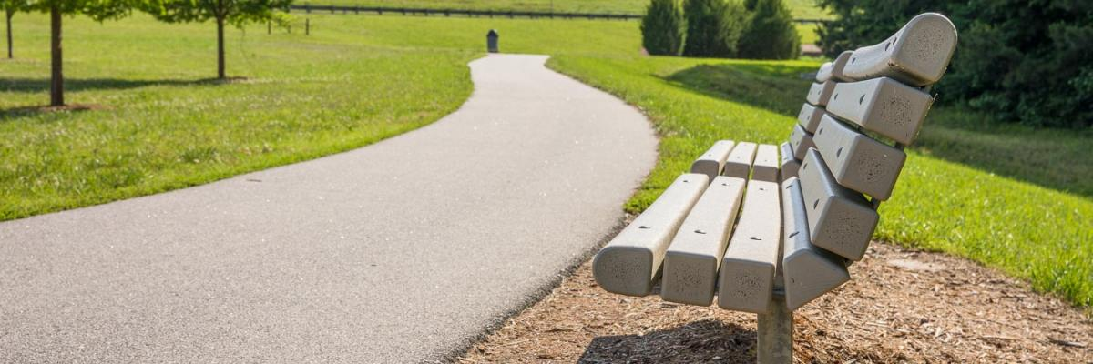 A paved trail running past a park bench with grassy slopes in the background.