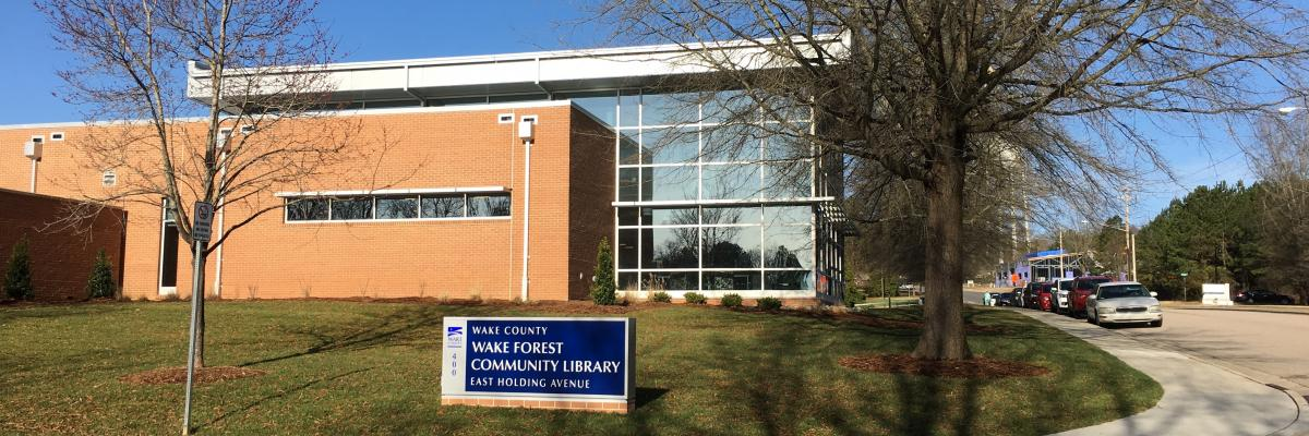 A picture of the Wake Forest Community Library from the street with the location sign