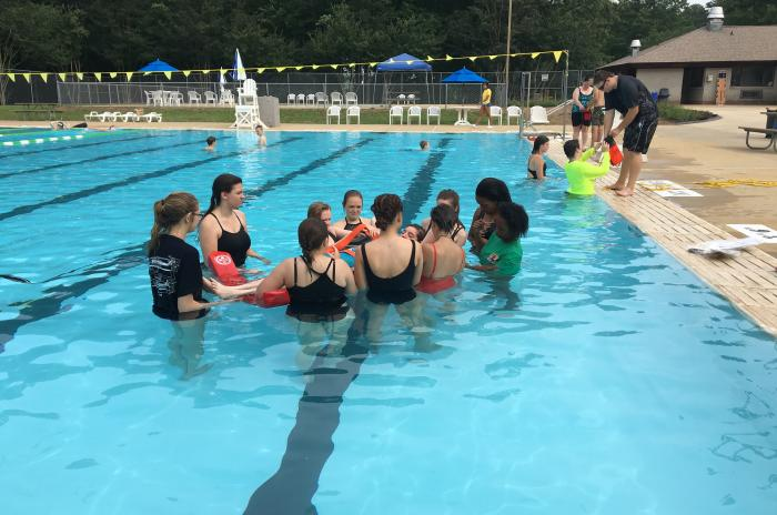 EMS camp participants in the pool learning water rescue skills