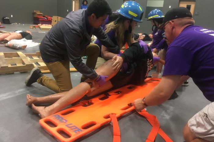EMS camp participants putting a patient on a backboard