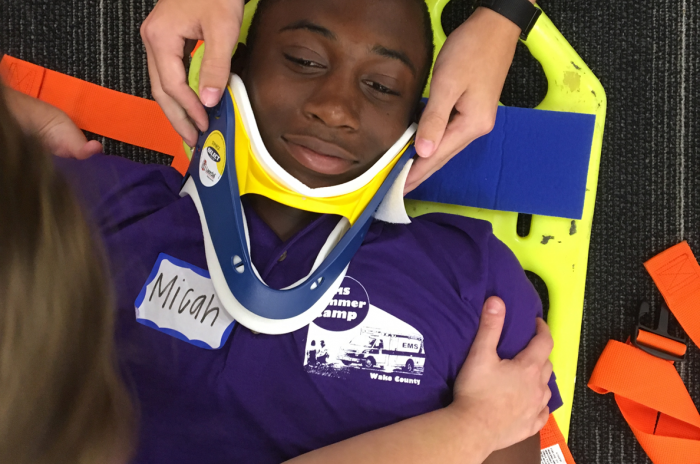EMS camp participant being fastened to a backboard in a training exercise