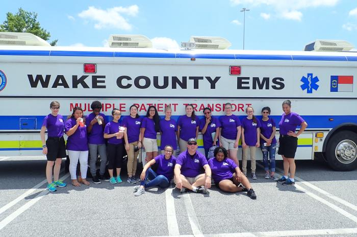 EMS camp participants posing in front of the multiple patient transport bus ambulance