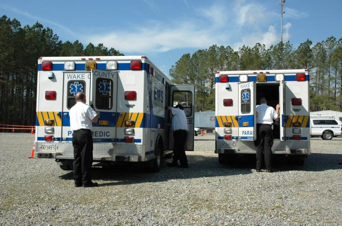 Two ambulances side by side with staff preparing for a drill
