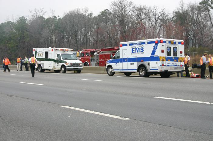 Two ambulances parked at a crash scene on a highway