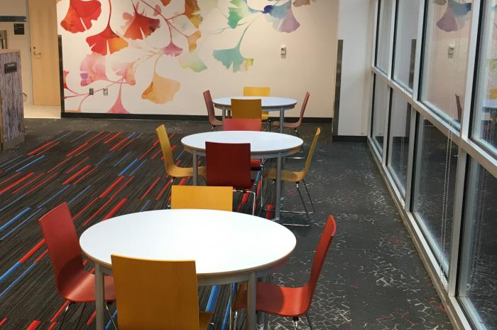 A picture of the Wake Forest Community Library Children's Program Area with round tables and chairs and a wall sized painting of orange and blue leaves on branches