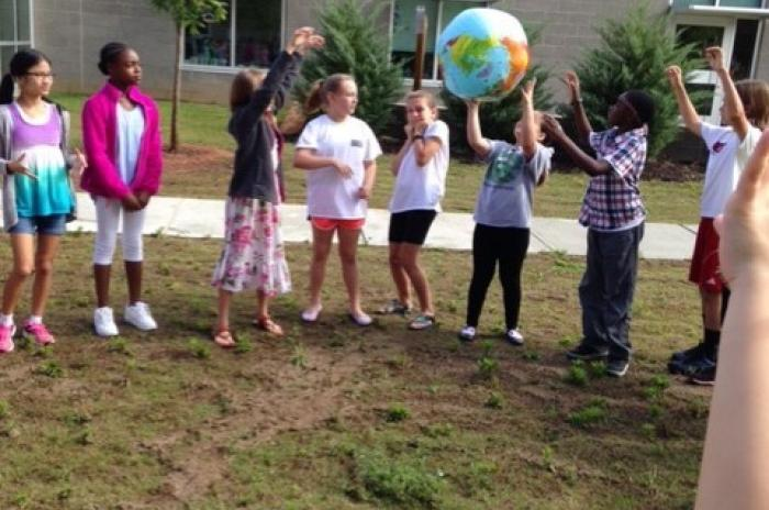 Students standing in a circle outside