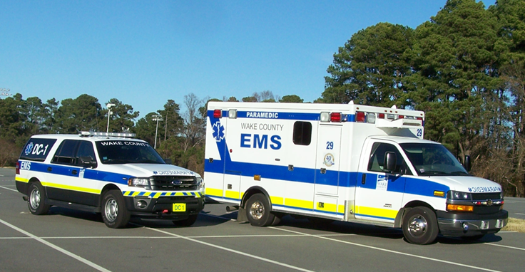 Wake County ambulance and district chief SUV under a beautiful blue sky.