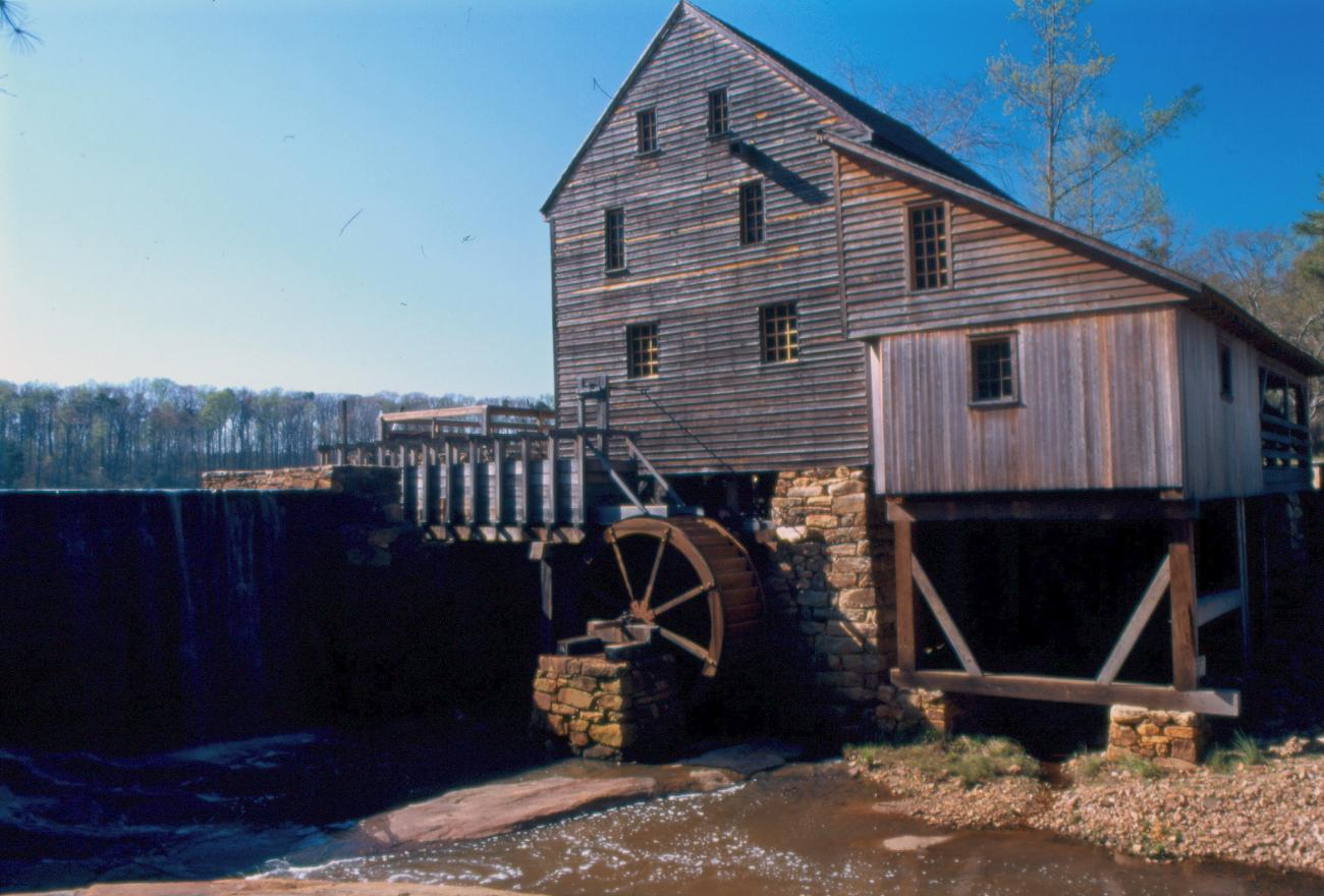 view of old historic wooden mill building with waterwheel beside of water dam