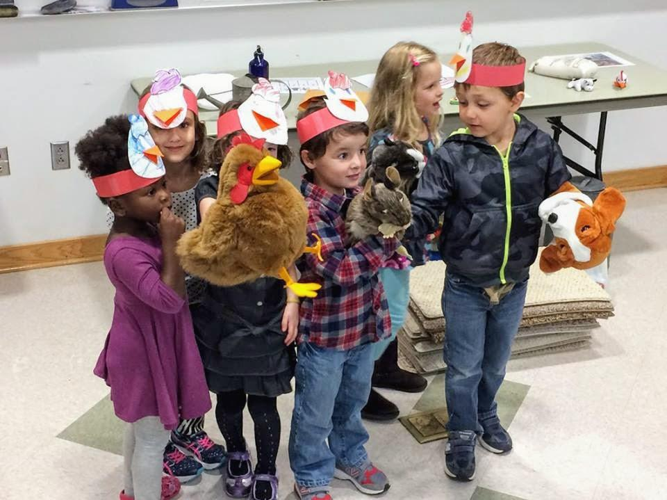 group of children play with puppets and wear chick hats inside classroom