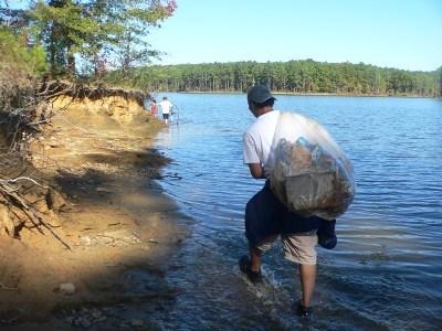 Man carrying bag of litter.