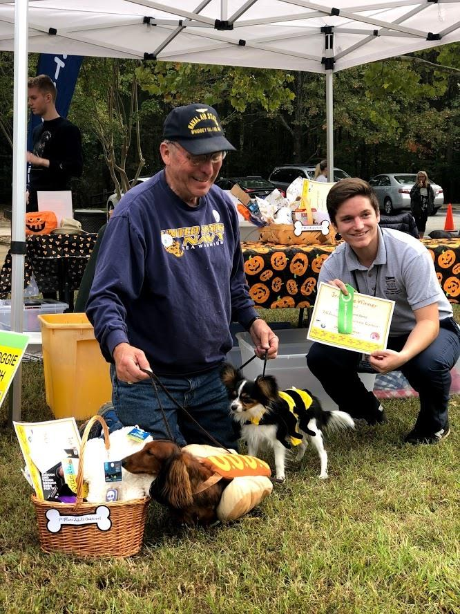 Man poses with park staff and two dogs in Halloween costumes to accept costume award