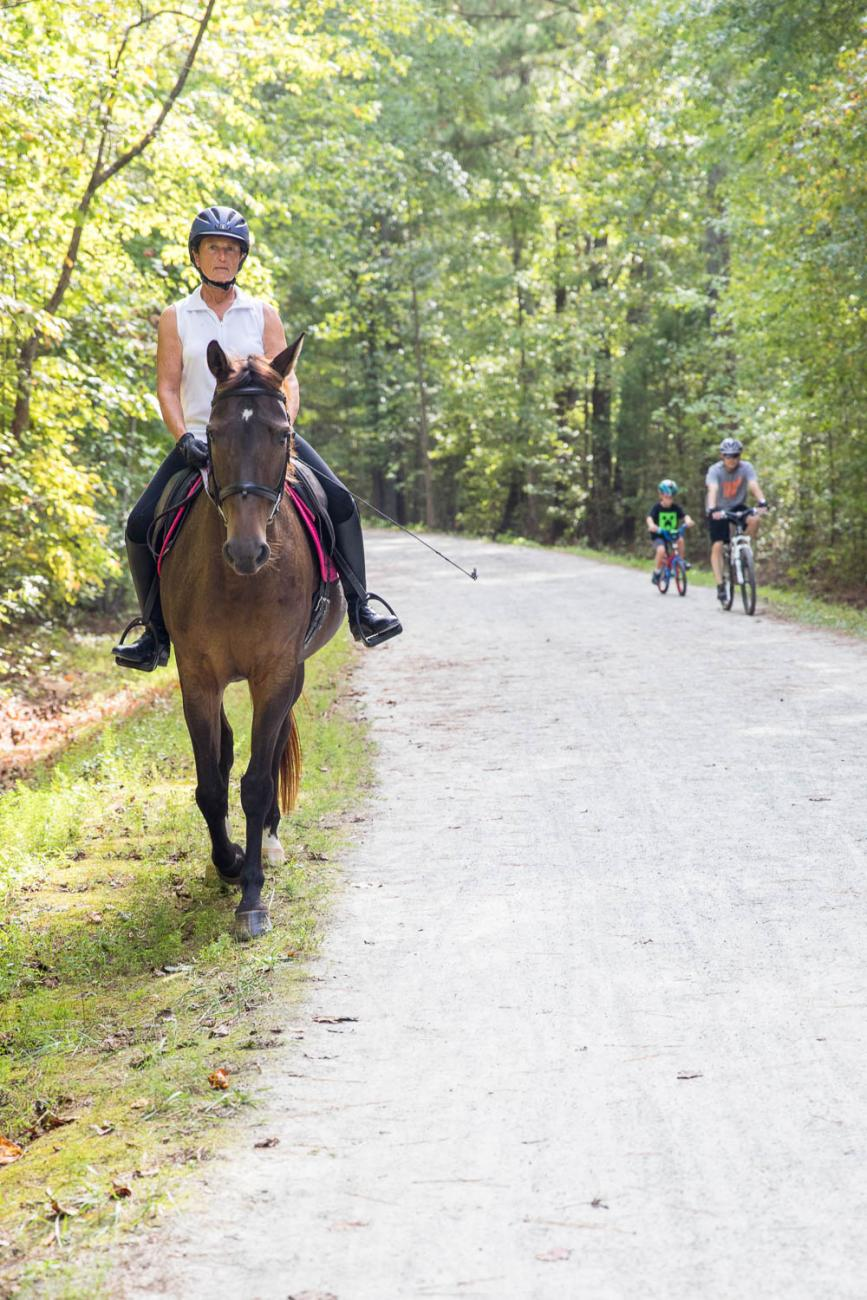 Photo of a horseback rider using the American Tobacco Trail with a father and son on bicycles in the background