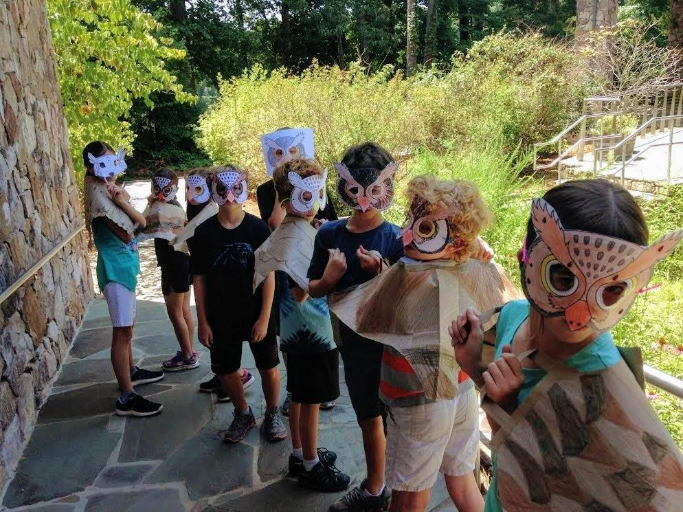 group of children stand outside with paper bag owl wings and owl masks