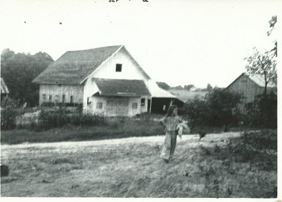 Black and white image of the Livestock Barn taken in the 1960s with girl running in front of barn