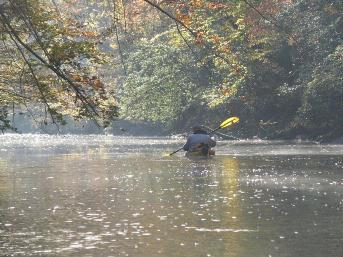 Picture of someone kayaking down the river