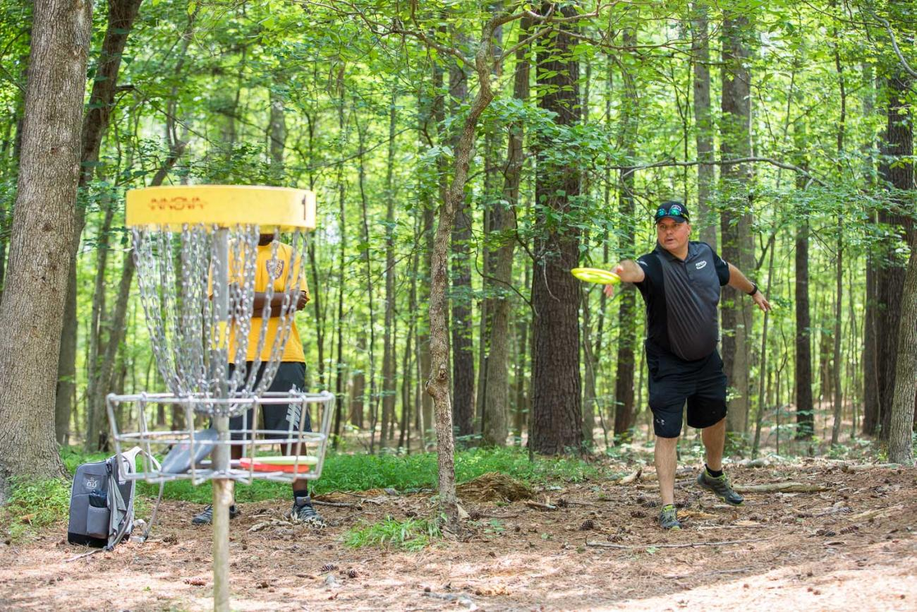 An individual playing the Buckhorn Disc Golf Course and throwing a disc at a basket