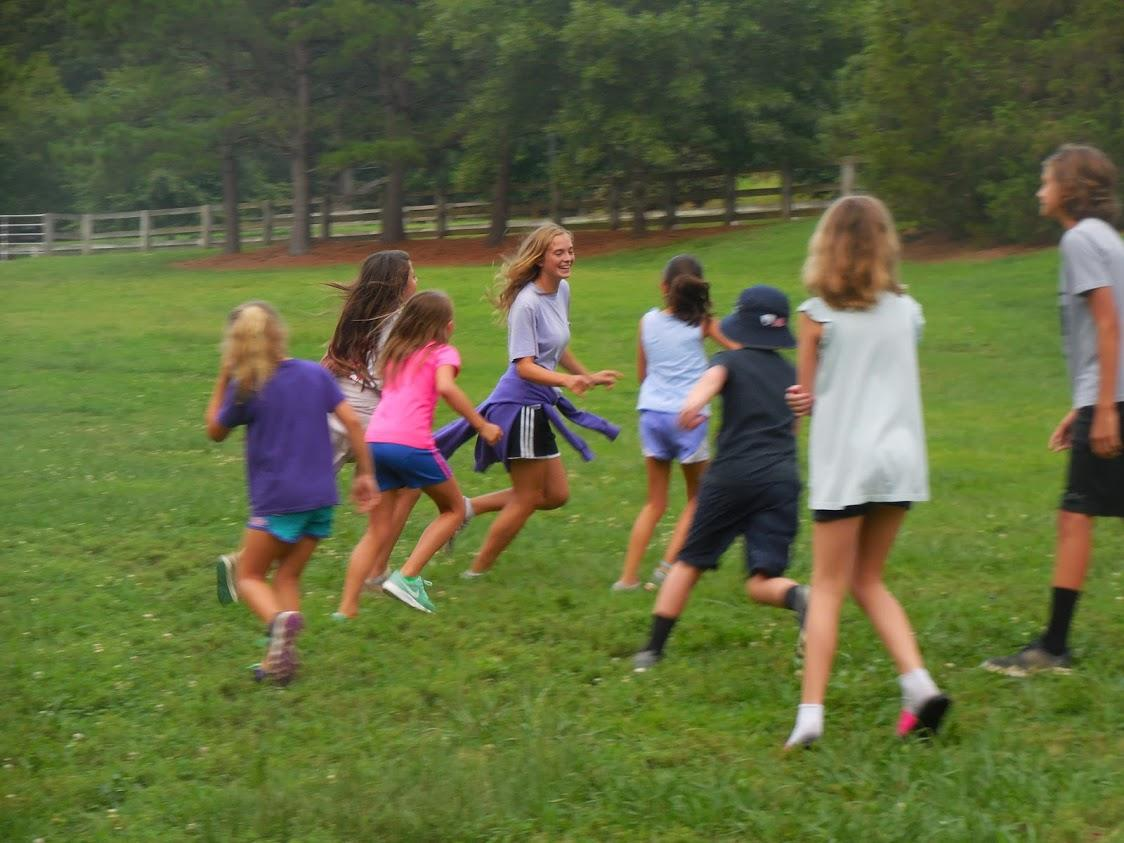 Group of children run and play tag in grassy field