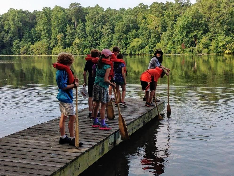 educator stands on boardwalk with group of children in pfds and shows them how to use canoe oars