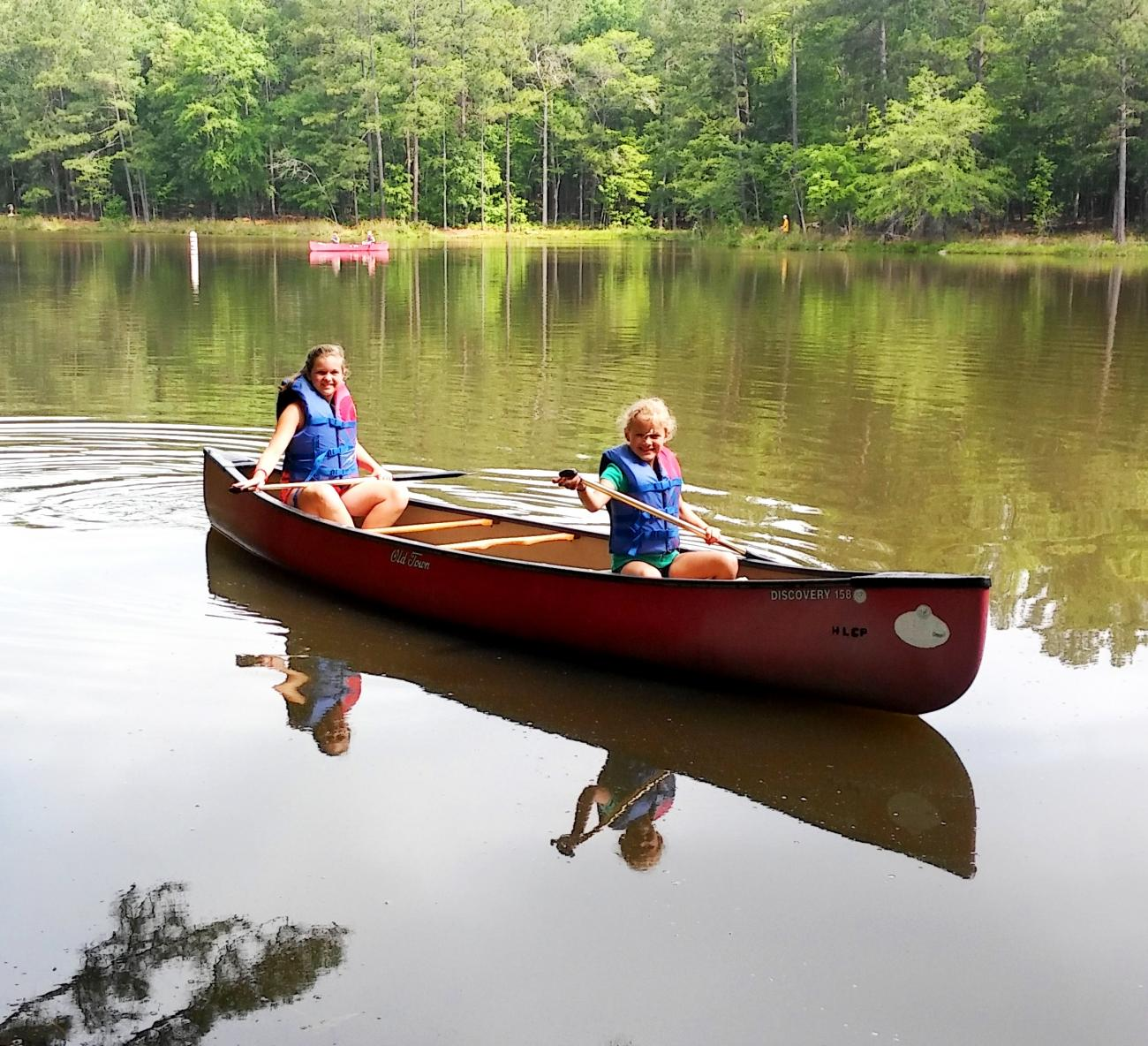 Photo of two campers in a canoe on the fishing pond