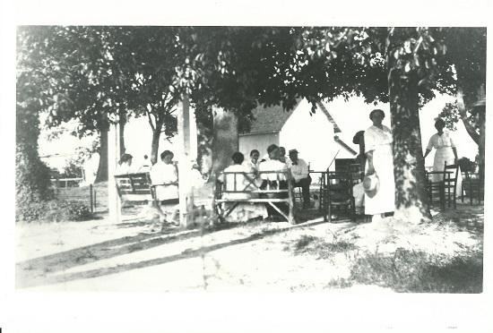 Black and white image of a picnic at Oak View after 1900 with the carriage house in the background