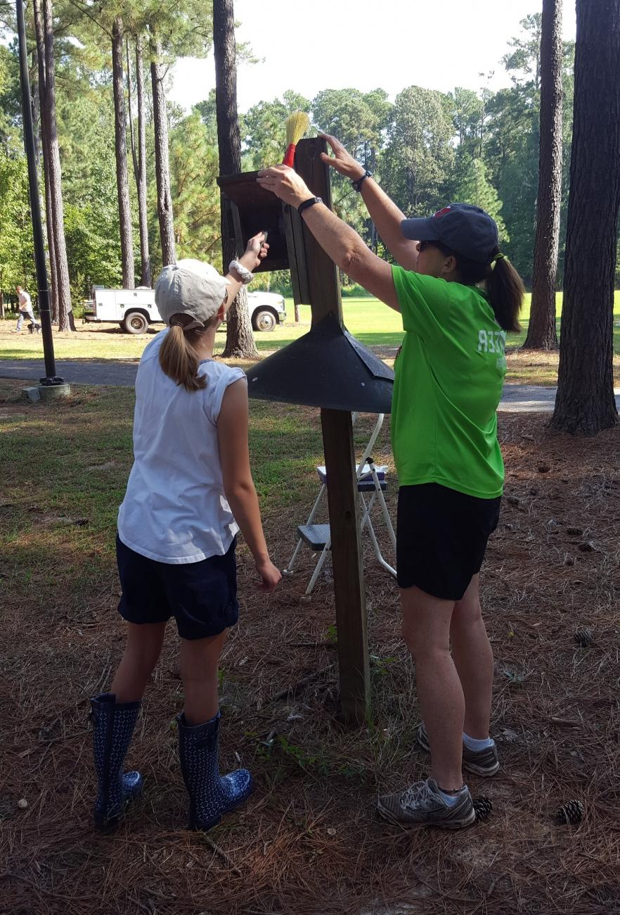 Photo of two volunteers cleaning a bluebird nest box during Citizen Science Thursday