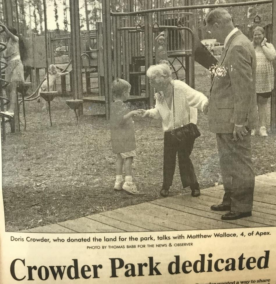 Newspaper clip of Doris Crowder with child at playground at park opening