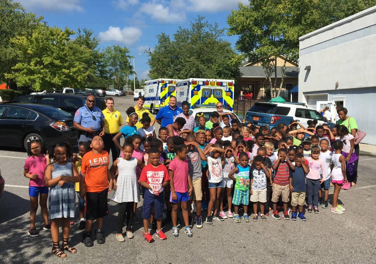 Many young children posing with paramedics in front of ambulances
