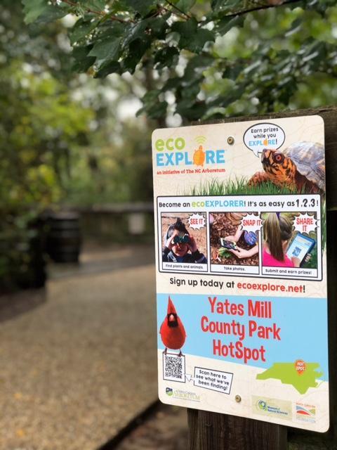 metal sign on wooden fence post promoting ecoexplore program